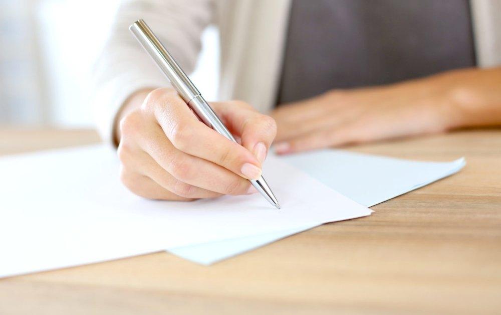 Женщина пишет заявление на работе
